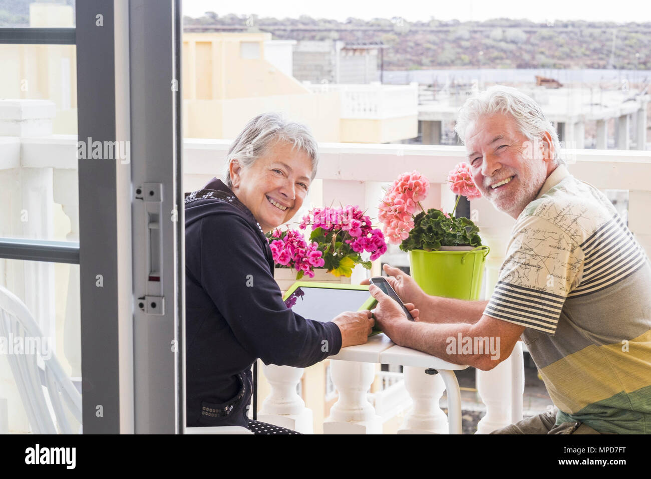 couple of happy seniors gentlemen use mobile technology tablet and phone outdoor in the terrace under a beautiful day sunlight. elderly retired daily  - Stock Image
