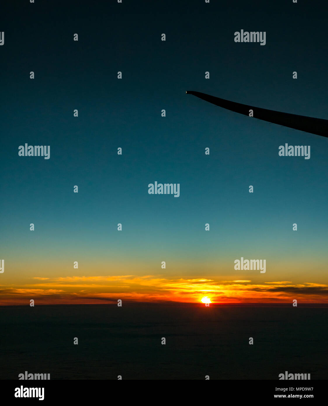 Orange sunset with clearly blue sky and low horizon, taken from aeroplane window, with airplane wing tip silhouette, take off from Heathro, London, UK - Stock Image