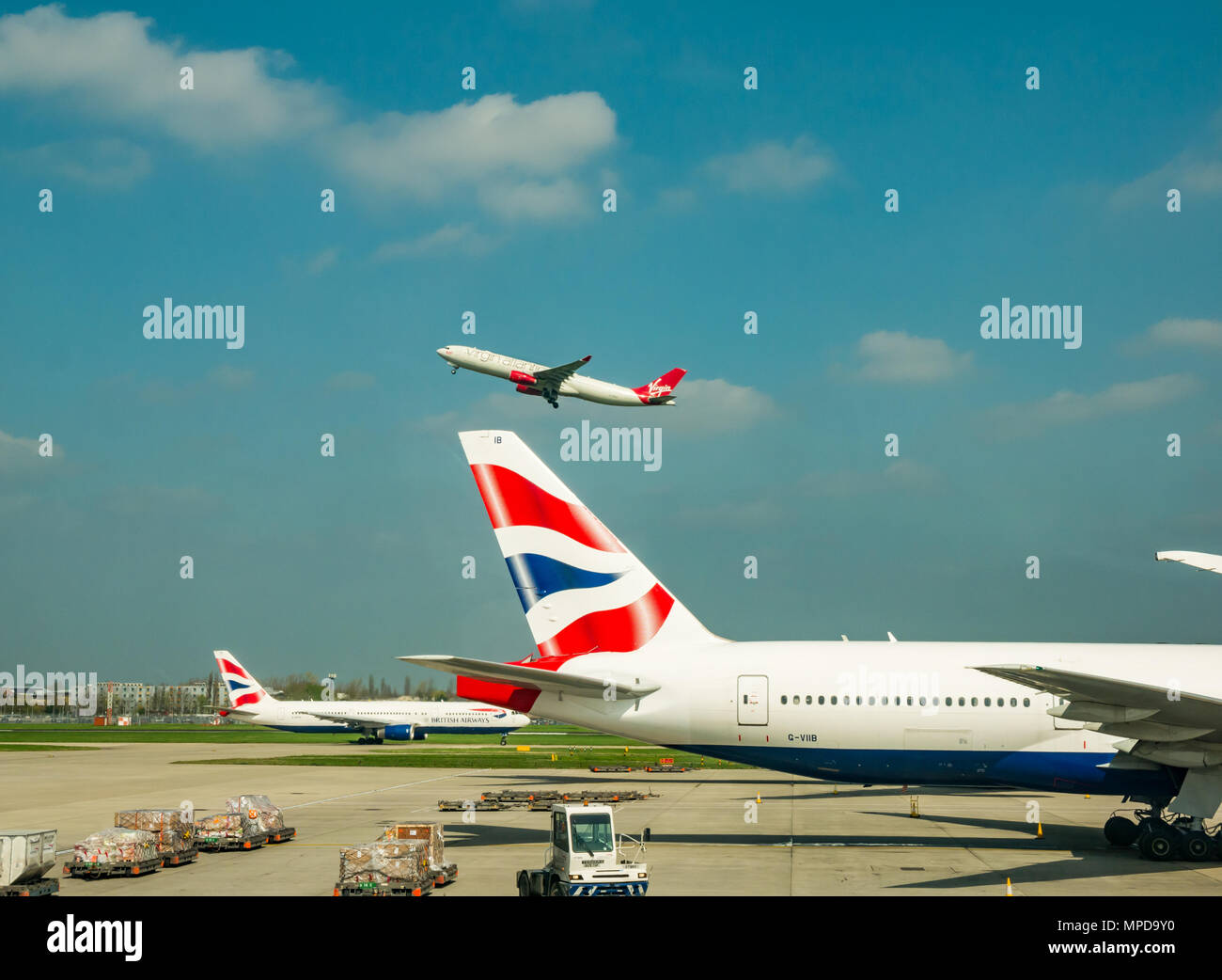 British Airways Boeing 777 on airport apron, Virgin Atlantic aeroplane taking off in blue sky, Terminal 5, Heathrow airport, London, England, UK Stock Photo