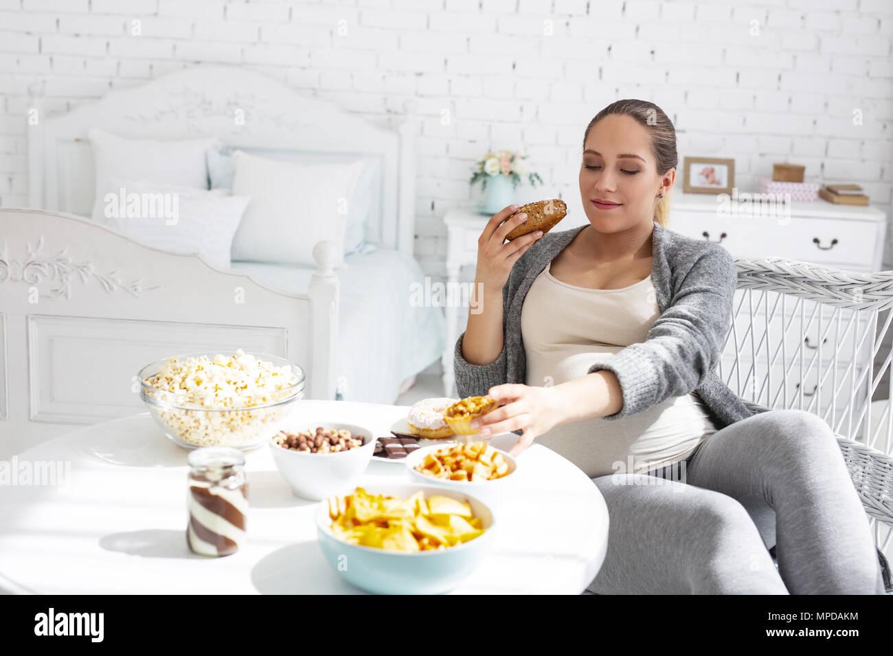 Glad pregnant woman tasting food - Stock Image