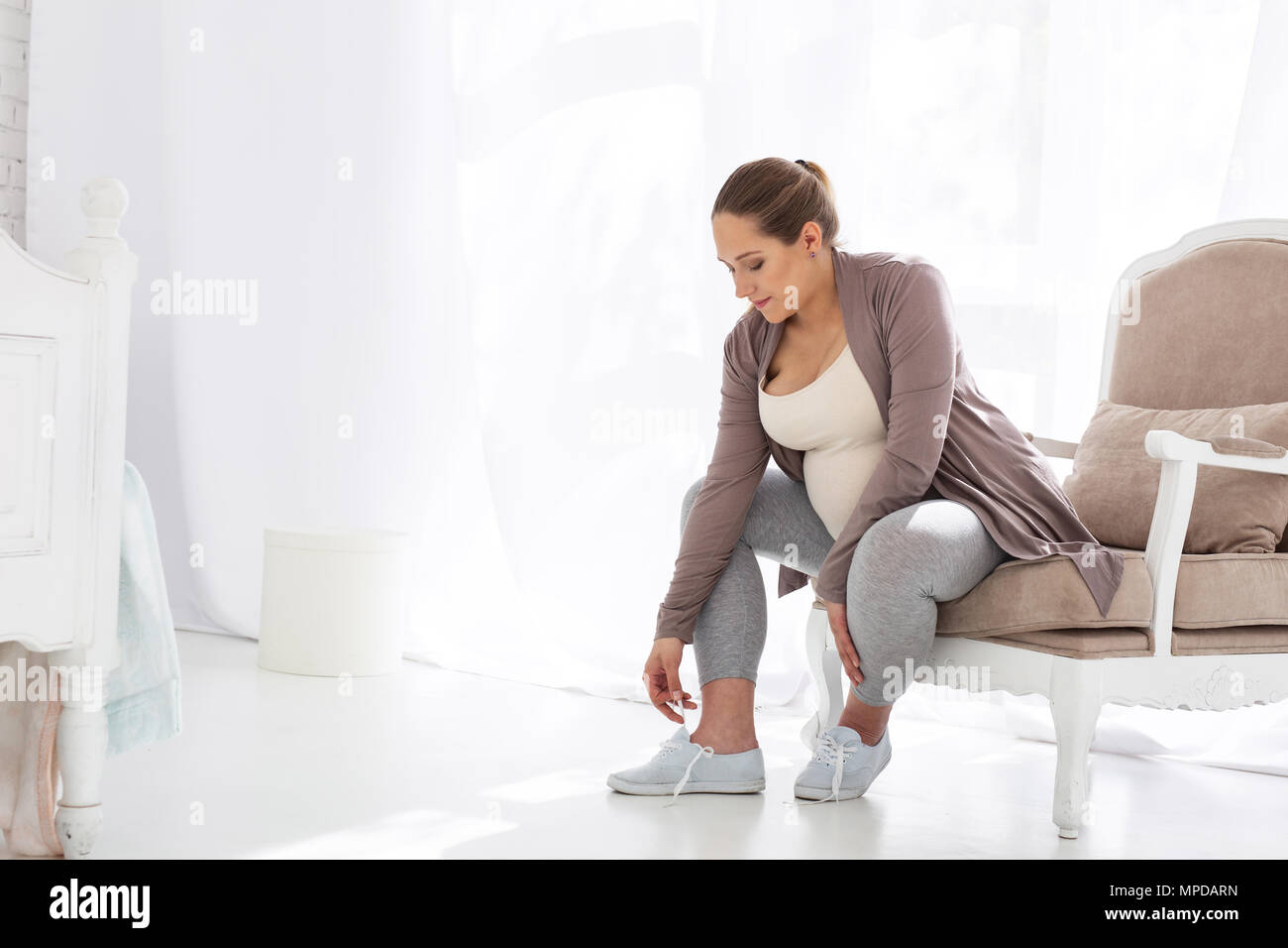 Focused pregnant woman putting on shoes - Stock Image