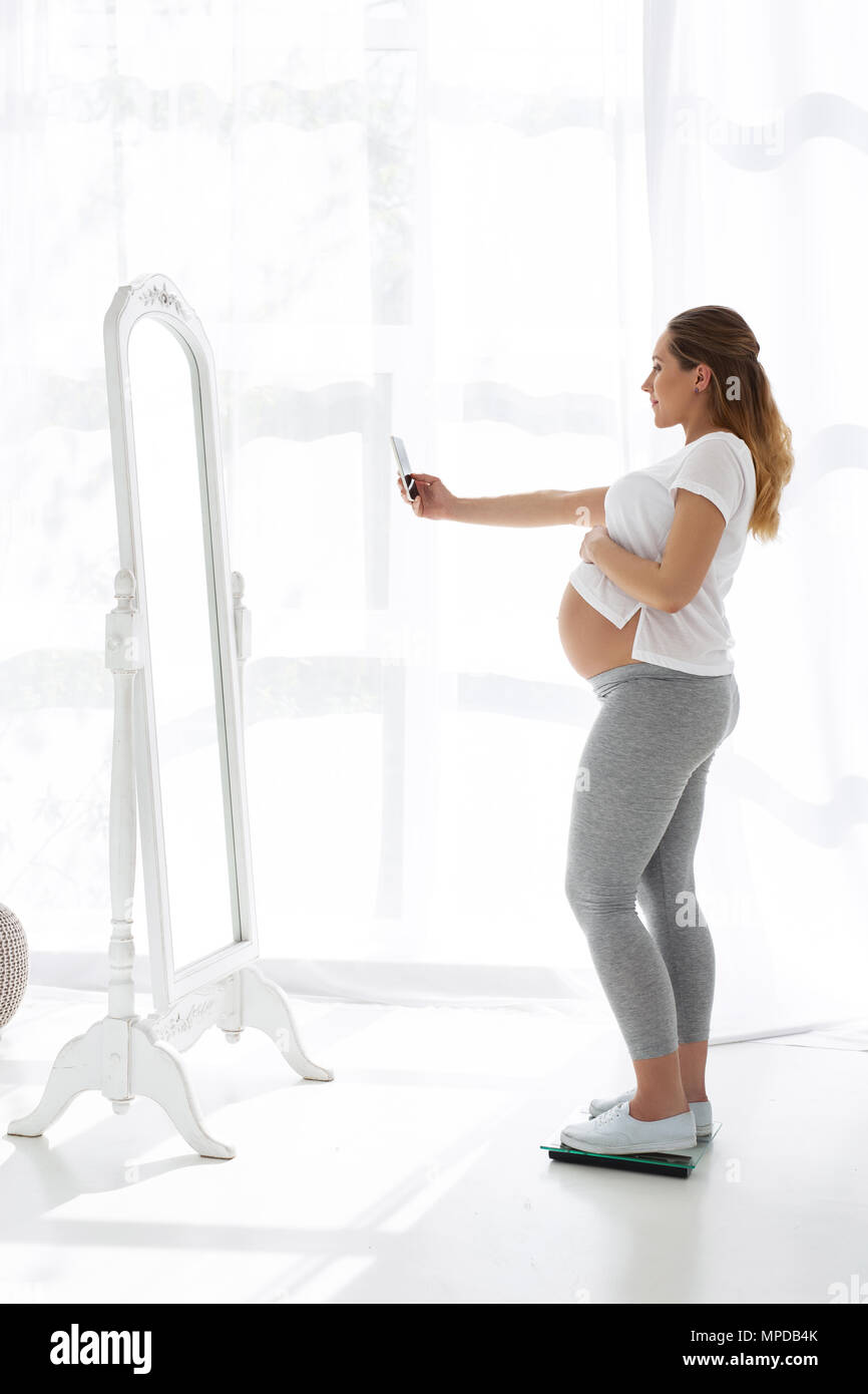 Cheerful pregnant woman taking selfie - Stock Image