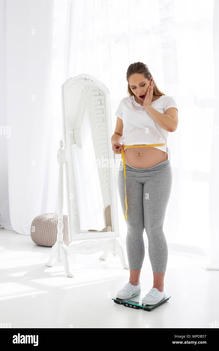 Surprised pregnant woman measuring size - Stock Image