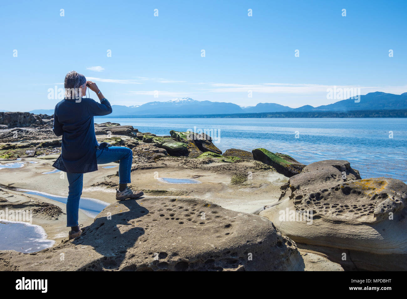 Young woman looking out to sea, Hornby Island, BC, Canada. - Stock Image