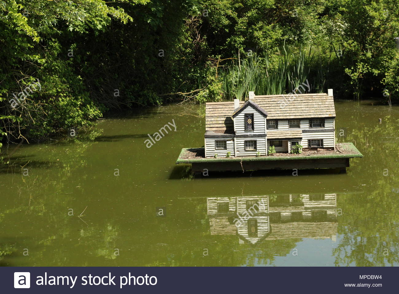 Miniature replica of the Ferry Boat Inn and reflections in a pond at North Fambridge, Essex, Britain. Space for copy. - Stock Image