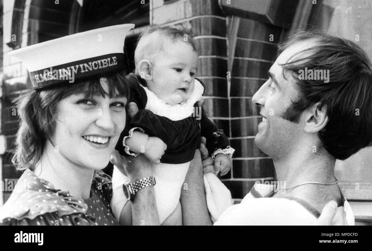 LEADING COOK CLIVE GRETTON SEES BABY STACEY FOR THE FIRST TIME WHEN HMS INVINCIBLE RETURNED FROM THE FALKLANDS HE WAS ALSO REUNITED WITH WIFE KAREN. PIC MIKE WALKER,  PORTSMOUTH 1982 - Stock Image