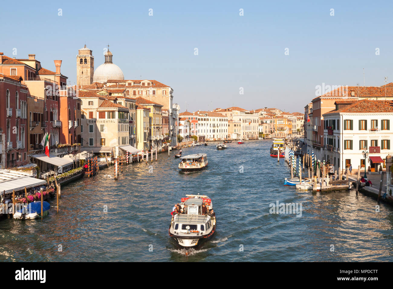 View of Grand Canal (Canal grande) at sunset from Scalzi Bridge, Venice, Veneto, Italy with vaporettos, (water bus, waterbus) full of tourists - Stock Image