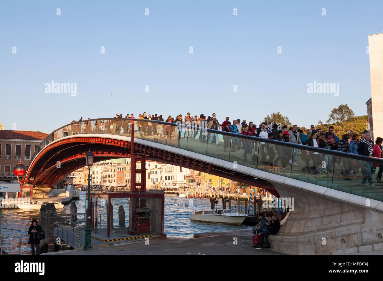 People crossing the Calatrava Bridge (Ponte della Costituzione), Grand Canal at sunset, dusk, golden hour, to Piazzale Roma, Venice,  Veneto, Italy - Stock Image