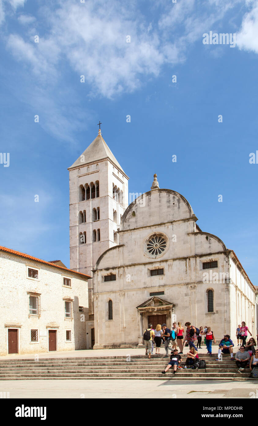 Holiday makers tourists and sightseers relaxing enjoying the spring sunshine outside St Mary's convent in the Adriatic coast resort of Zadar Croatia - Stock Image