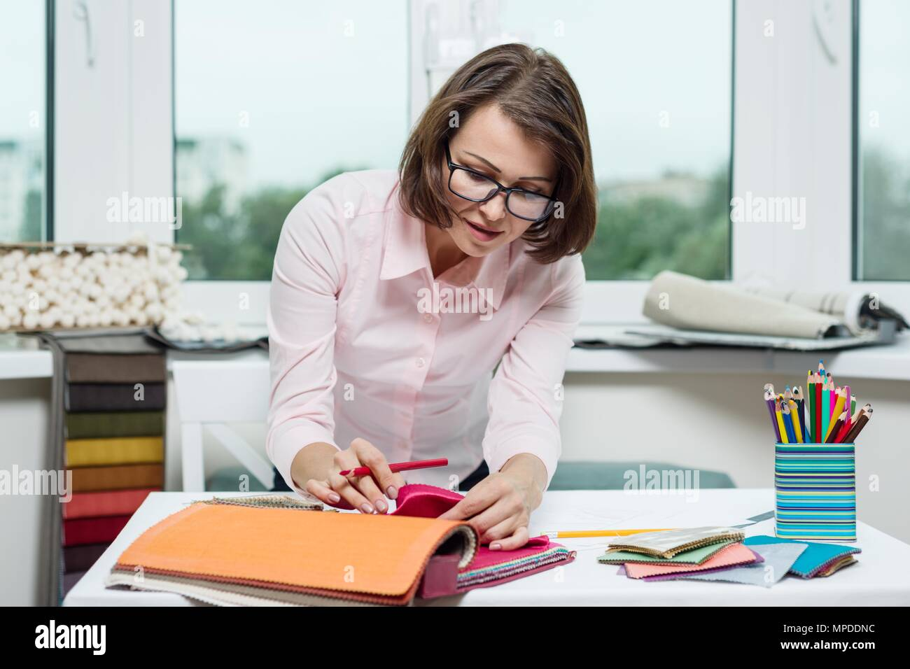 woman interior designer works with samples of fabrics for curtains