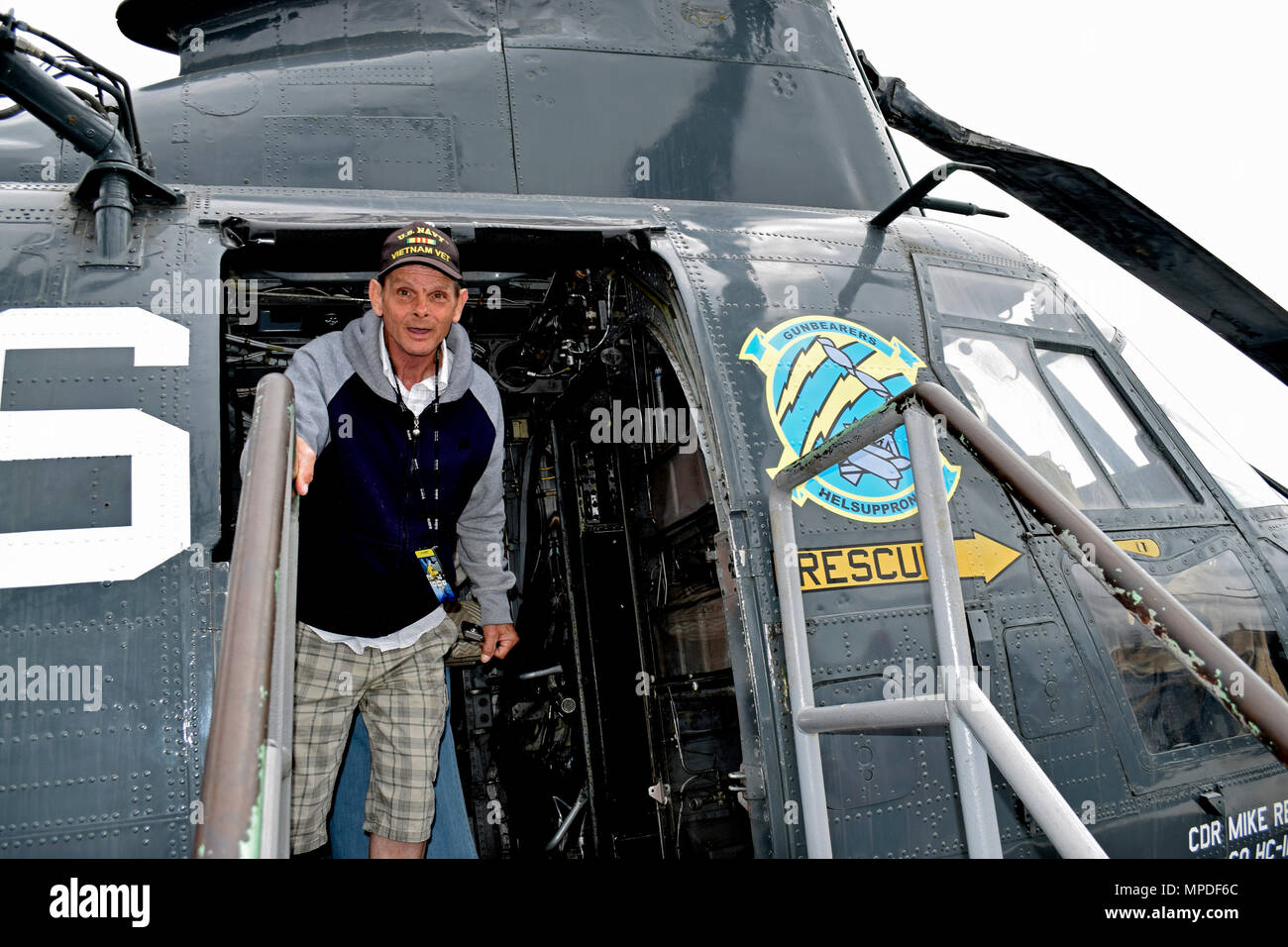Navy Vietnam Veteran, Wayne Oversen, tours a helicopter on the flight deck of the USS Midway Museum, San Diego, California - Stock Image