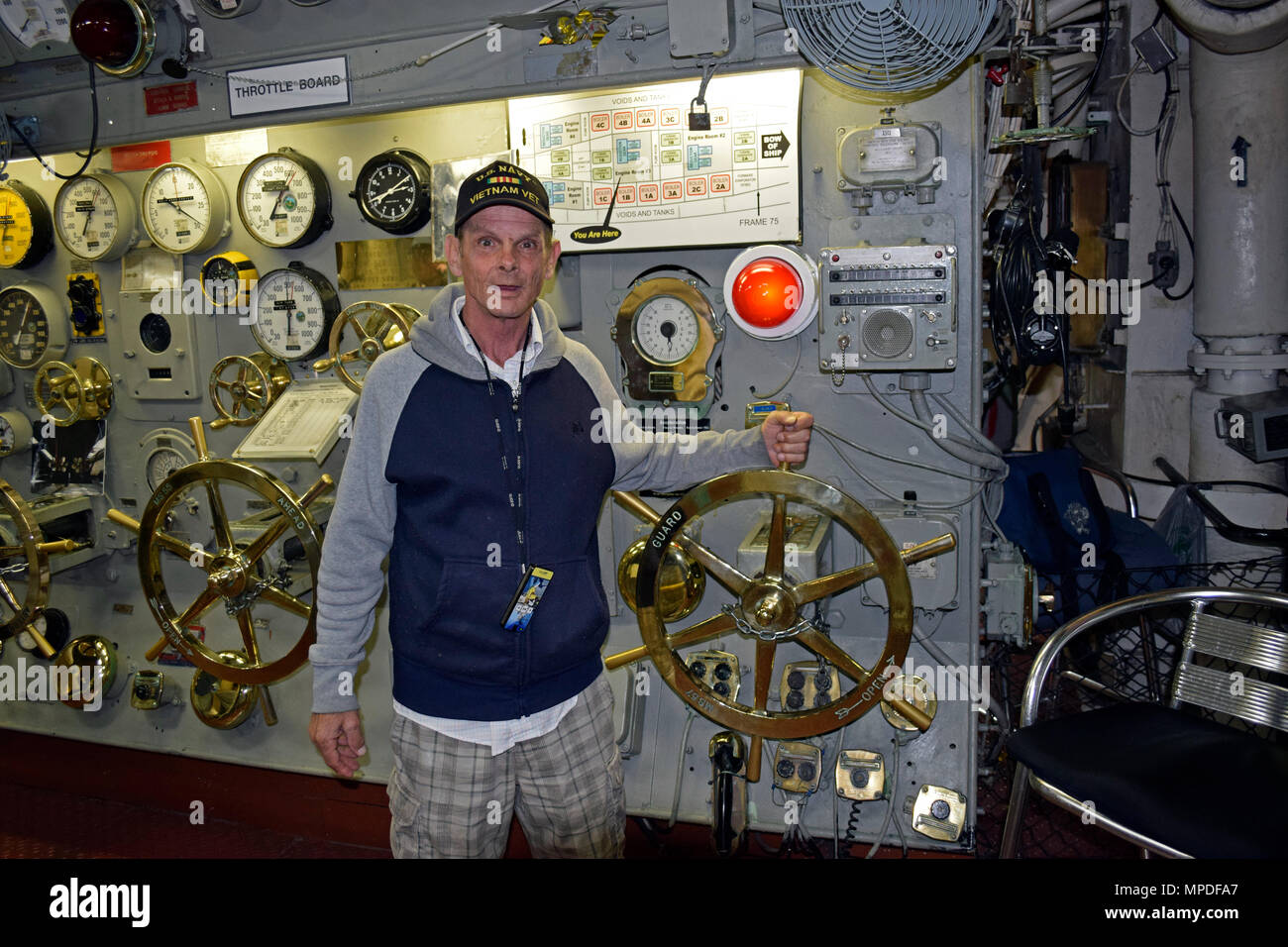 US Navy Vietnam Veteran hand on the throttle in the engine room, control room, of the USS Midway aircraft carrier Museum, San Diego, California Stock Photo