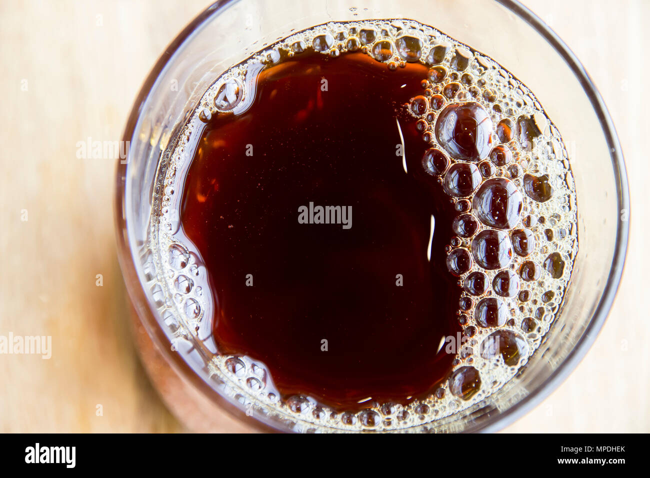Freshly Brewed Coffee With Bubbles And Flare In Glass On Table Top