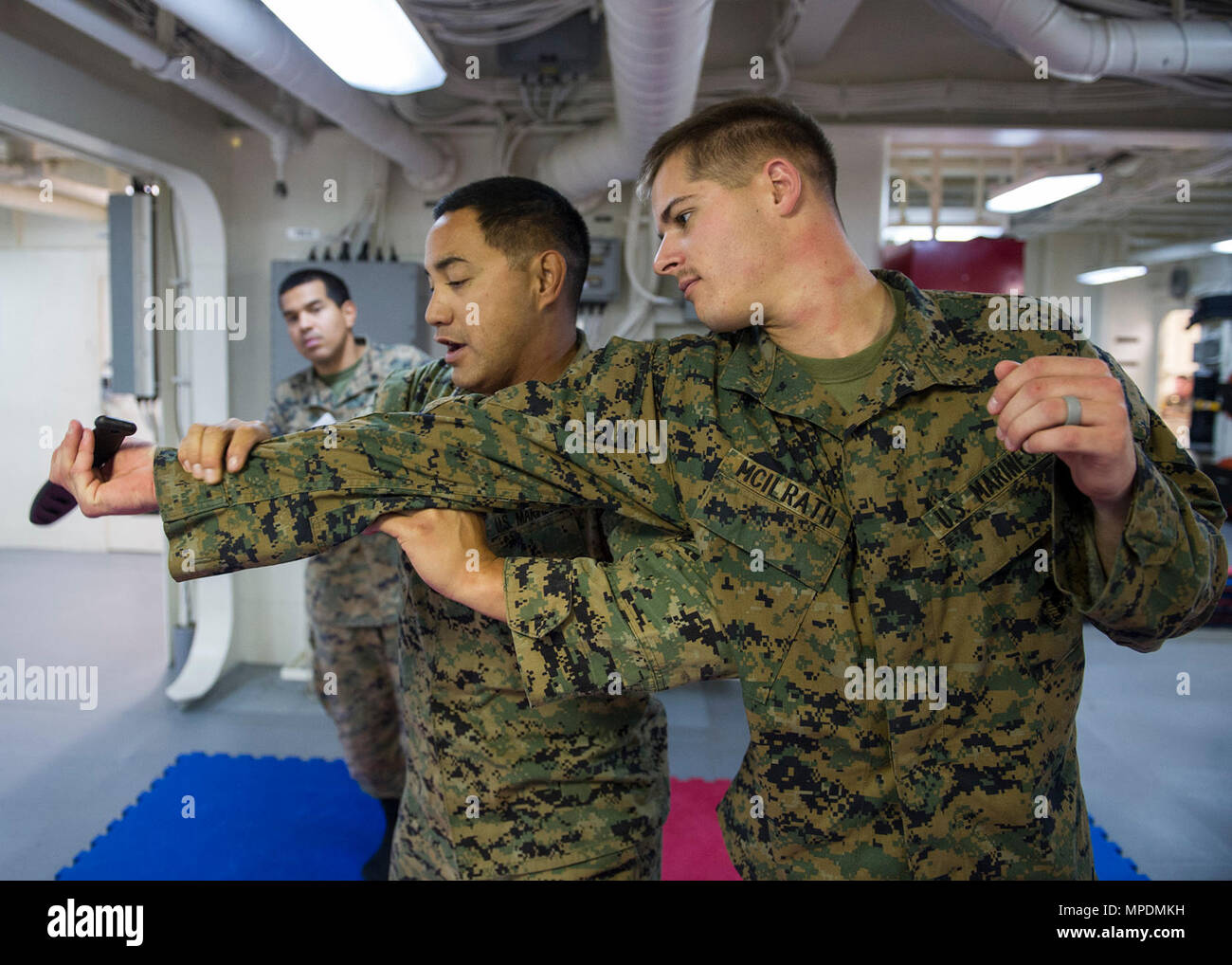 PACIFIC OCEAN (April 10, 2017) Marine Lance Cpl. Stefan Mcilrath (right) and Staff Sgt. Kaluaokal Kaiahua (left), assigned to Marine Expeditionary Unit (MEU) 15, practice mixed martial arts during a Marine Corps Martial Arts Program (MCMAP) training exercise aboard the amphibious assault ship USS America (LHA 6). America is currently underway with more than 1,000 Sailors and 1,600 embarked Marines conducting Amphibious Squadron/Marine Expeditionary Unit Integration operations in preparation for the ship's maiden deployment later this year. - Stock Image