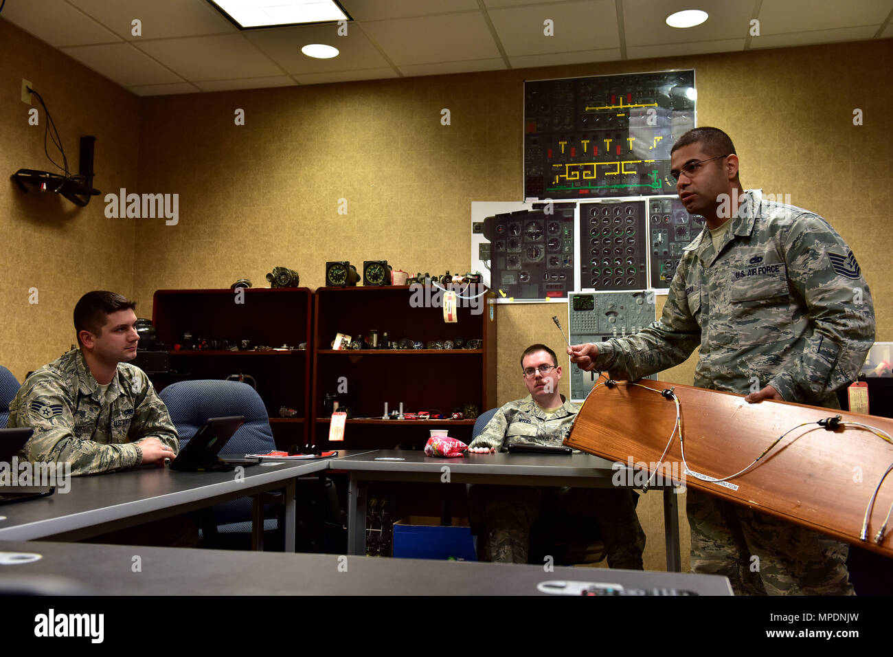 U.S. Air Force Tech. Sgt. Jose Piedra, standing, 373rd Training Squadron Detachment 4 production supervisor and instructor, discusses the importance of the 1553B databus backbone cable for the C-130J to his students Feb. 23, 2017 at the Center of Excellence on Little Rock Air Force Base, Ark.  The cable transfers critical information between the computer systems throughout the aircraft and the Airmen are responsible for the understanding how they work. (U.S. Air Force photo by Staff Sgt. Jeremy McGuffin) - Stock Image