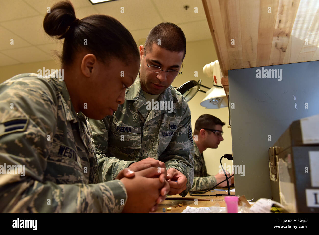 U.S. Air Force Tech. Sgt. Jose Piedra, center, 373rd Training Squadron Detachment 4 production supervisor and instructor, demonstrates splicing and building a 1553B databus cable to Airman 1st Class Shania Westin, left, 373rd TRS student, for the C-130J Feb. 23, 2017 at the Center of Excellence on Little Rock Air Force Base, Ark.  The Airman must understand how the cable functions as it transfers information throughout the aircraft and be able to build new ones effectively. (U.S. Air Force photo by Staff Sgt. Jeremy McGuffin) - Stock Image