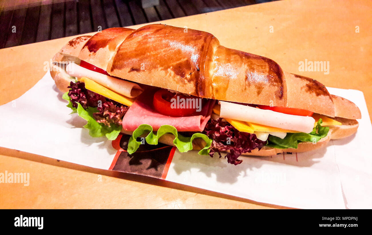 Croissant Sandwich with ham, cheddar cheese, cherry tomato and greens. fast food concept. Stock Photo