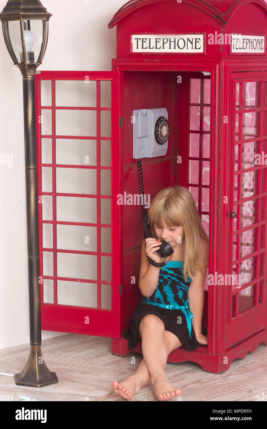 child girl calling in red in a phone - Stock Image