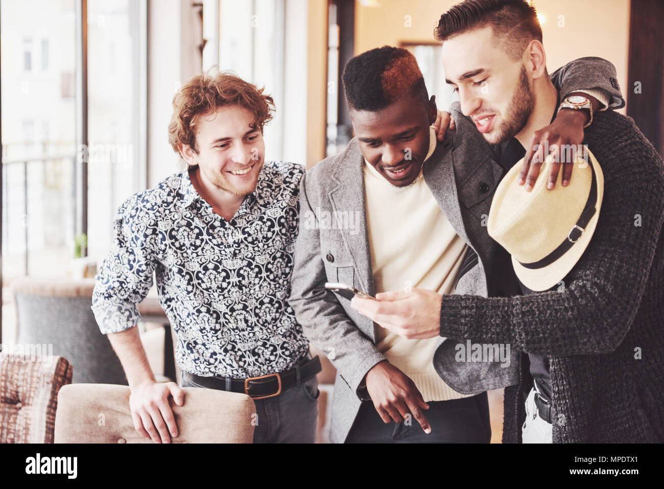 Cheerful old friends communicate with each other and phone watch in pub. Concept of entertainment and lifestyle. Wifi connected people in bar table meeting - Stock Image
