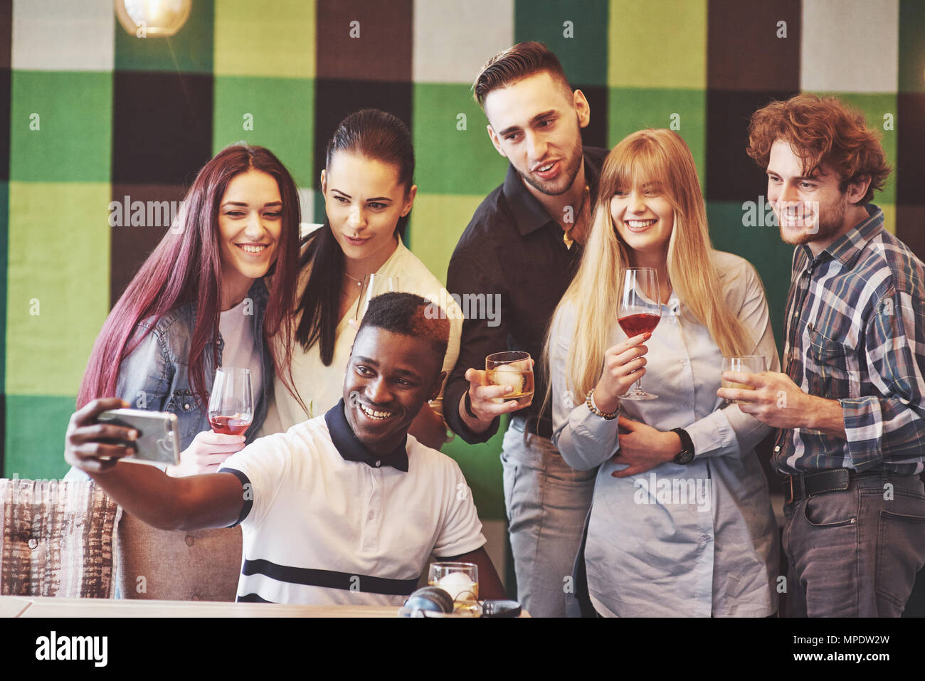 Friends having fun at restaurant.Two boys and four girls drinking making selfie, making peace sign and laughing. On foreground woman holding smart phone. All wear casual clothes - Stock Image