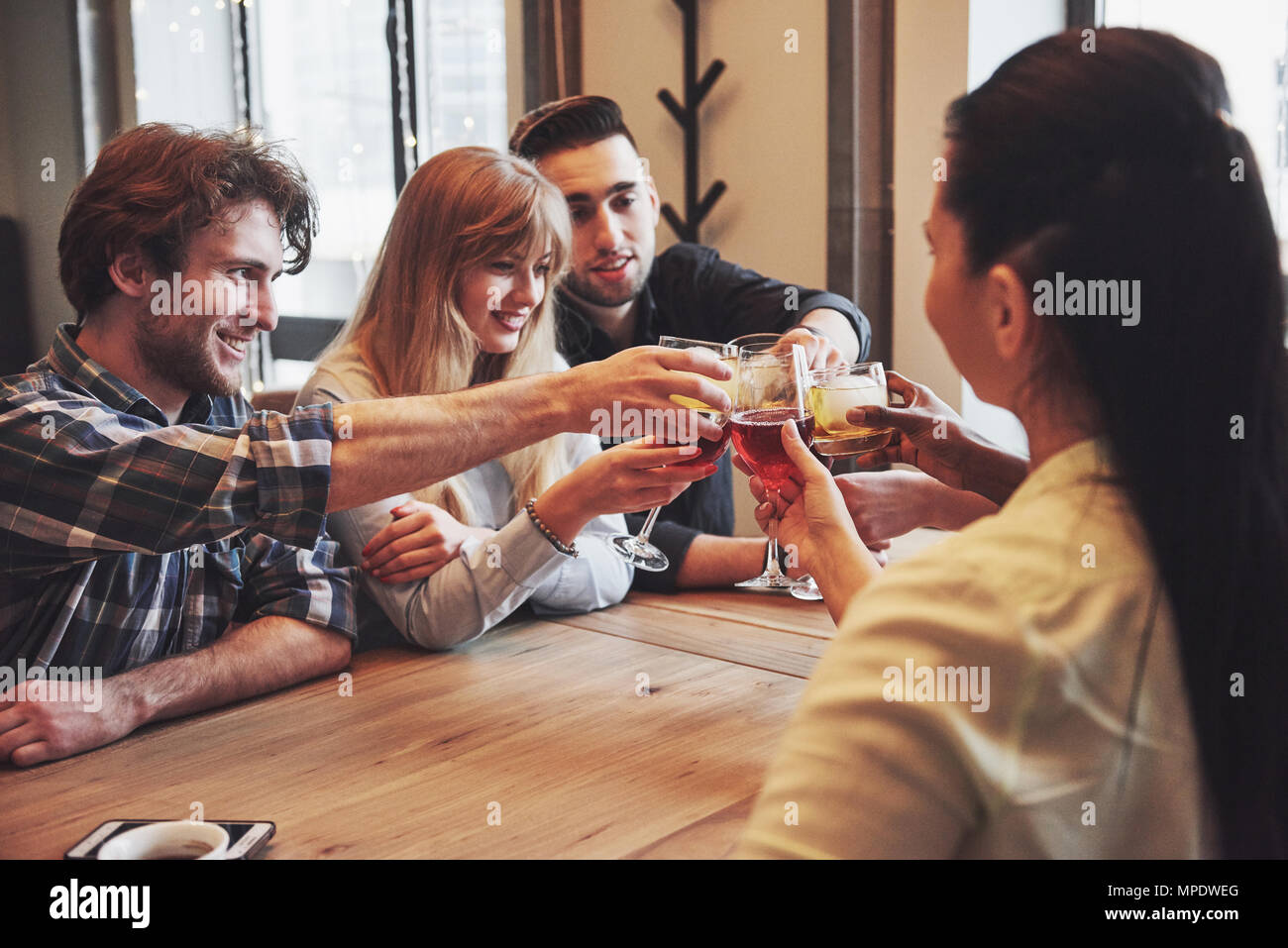 Group of young friends having fun and laughing while dining at table in restaurant - Stock Image