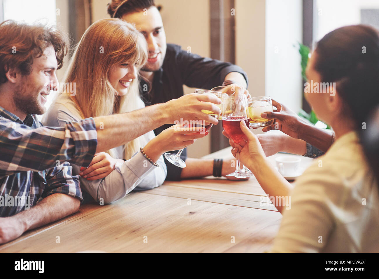 Hands of people with glasses of whiskey or wine, celebrating and toasting in honor of the wedding or other celebration - Stock Image