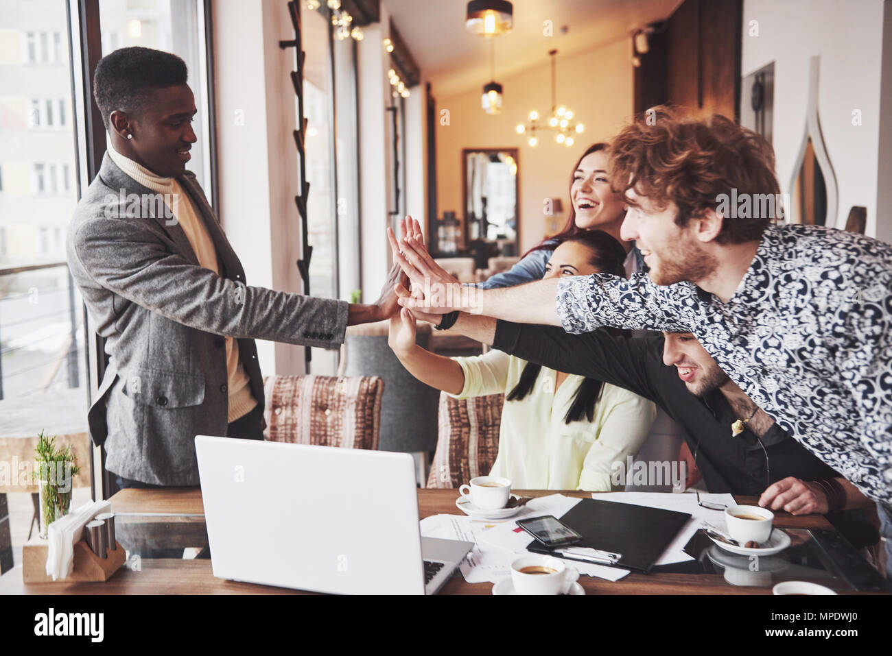 Happy young entrepreneurs in casual clothes at cafe table or in business office giving high fives to each other as if celebrating success or starting new project - Stock Image