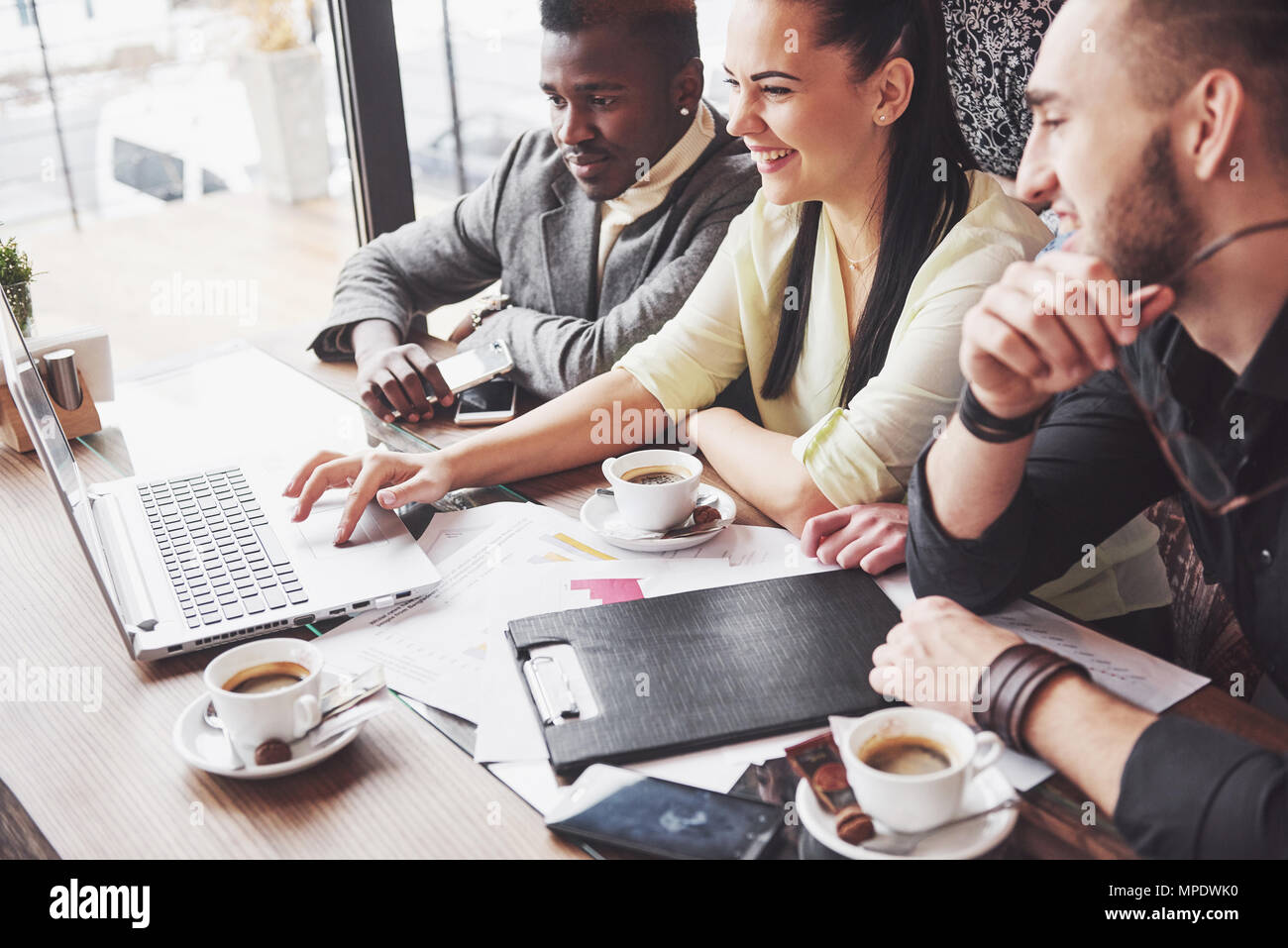Multi ethnic business people, entrepreneur, business, small business concept, Woman showing coworkers something on laptop computer as they gather around a conference table - Stock Image