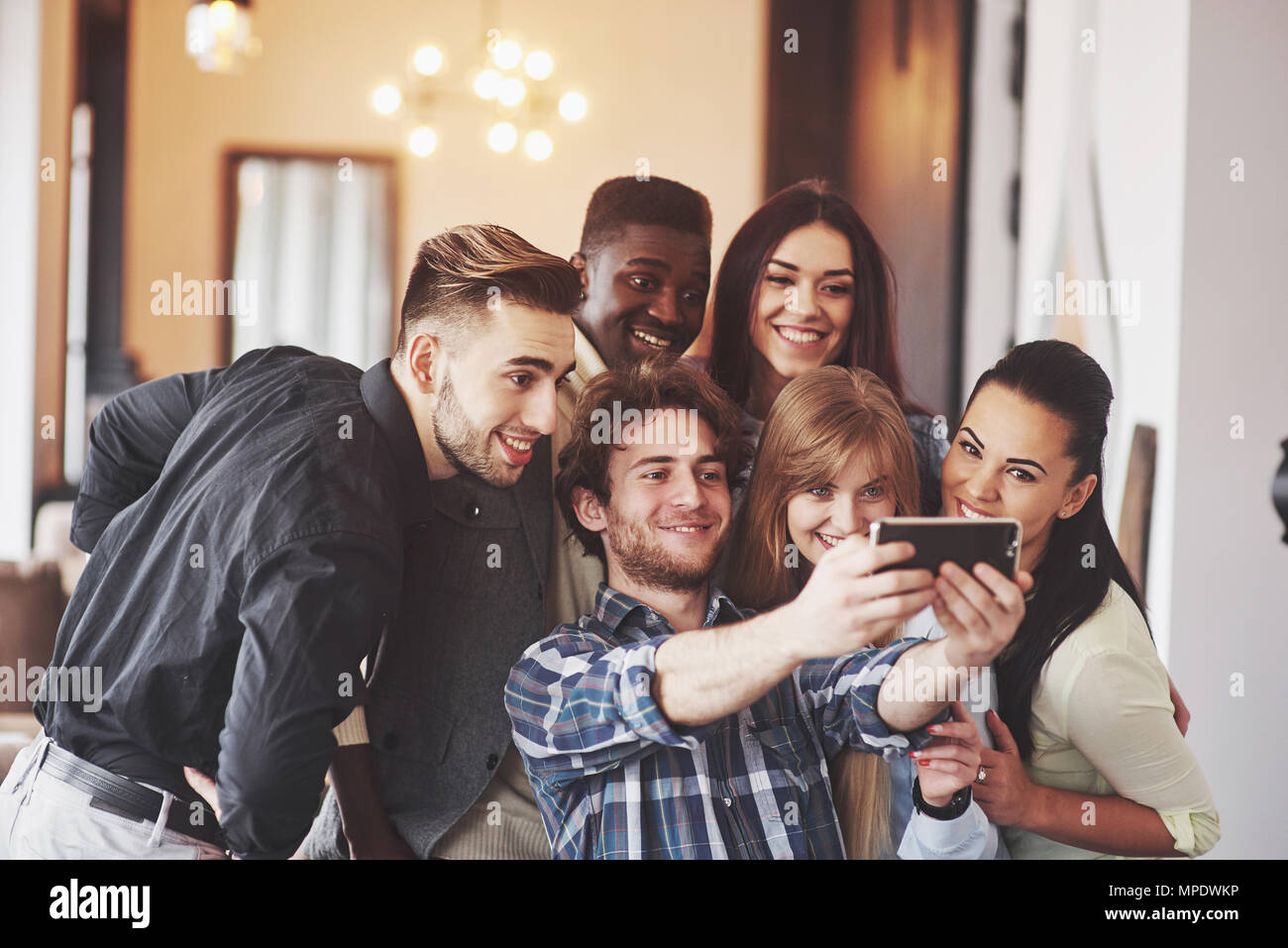 Multiracial people having fun at cafe taking a selfie with mobile phone. Group of young friends sitting at restaurant taking self portrait with smart phone Stock Photo