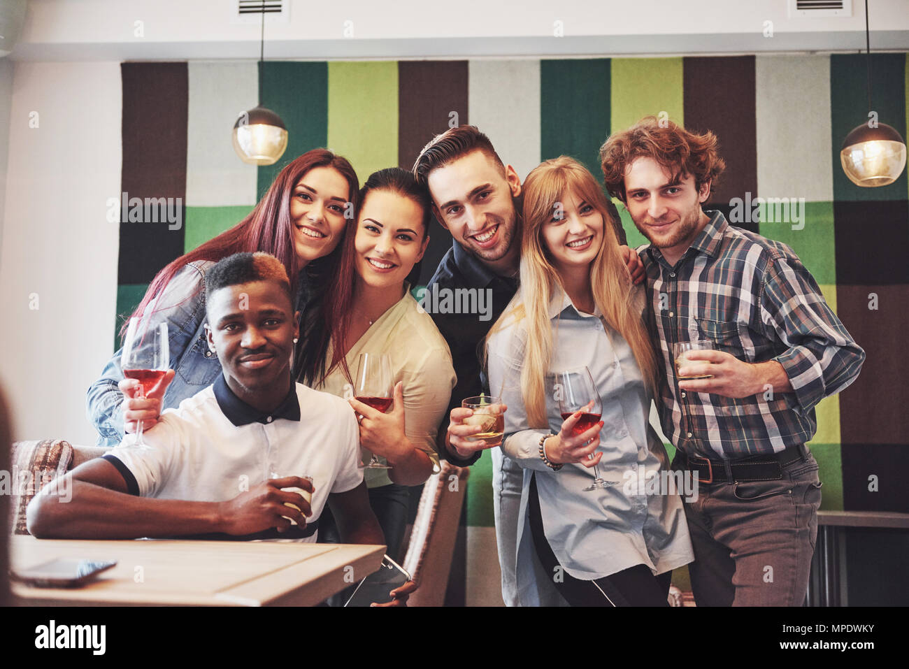 Multiracial people having fun at cafe taking a selfie with mobile phone. Group of young friends sitting at restaurant - Stock Image