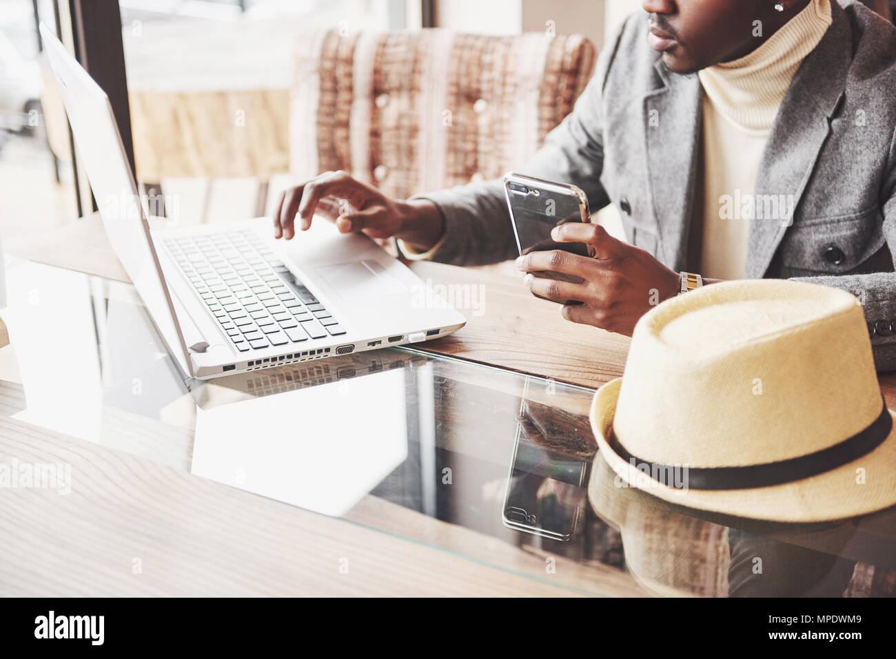 Pensive afro american handsome professional writer of popular articles in blog dressed in trendy outfit and glasses thinking over new story proofreading his script from notebook sitting in cafe - Stock Image