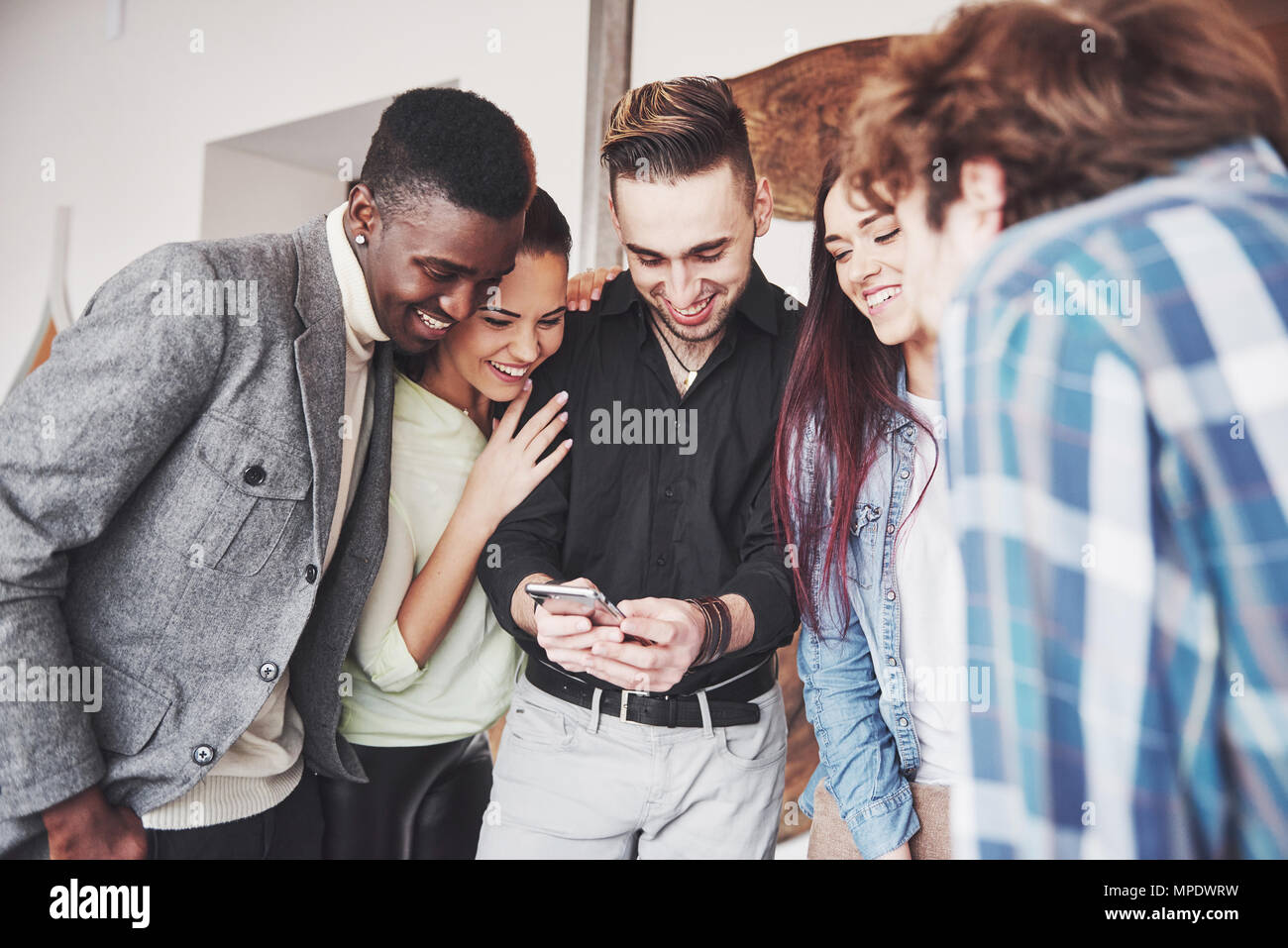 Portrait of cheerful young friends looking at smart phone while sitting in cafe. Mixed race people in restaurant using mobile phone - Stock Image