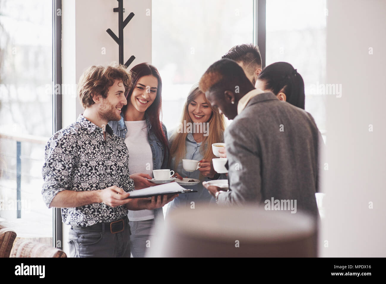 Successful business people are using gadgets, talking and smiling during the coffee break in office - Stock Image