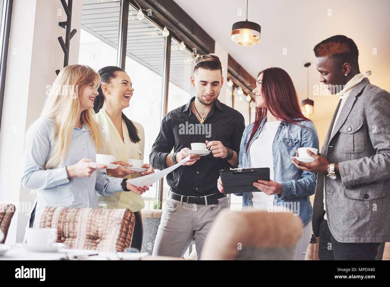 Successful young business people are talking and smiling during the coffee break in office - Stock Image