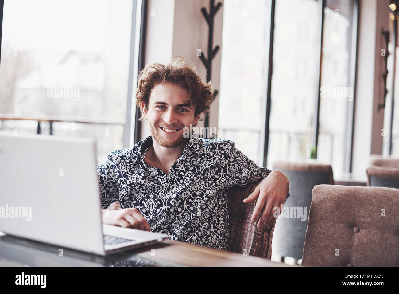 Young handsome man sitting in office with cup of coffee and working on project connected with modern cyber technologies. Businessman with notebook trying to keep deadline in digital marketing sphere - Stock Image