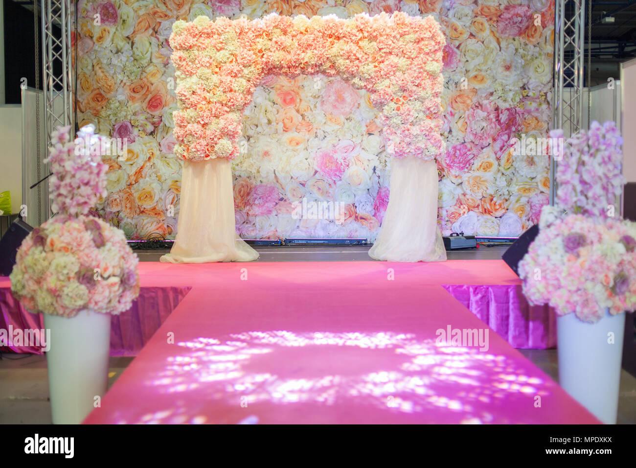 Beautiful wedding arch on the podium vases with flowers stand along beautiful wedding arch on the podium vases with flowers stand along the catwalk izmirmasajfo