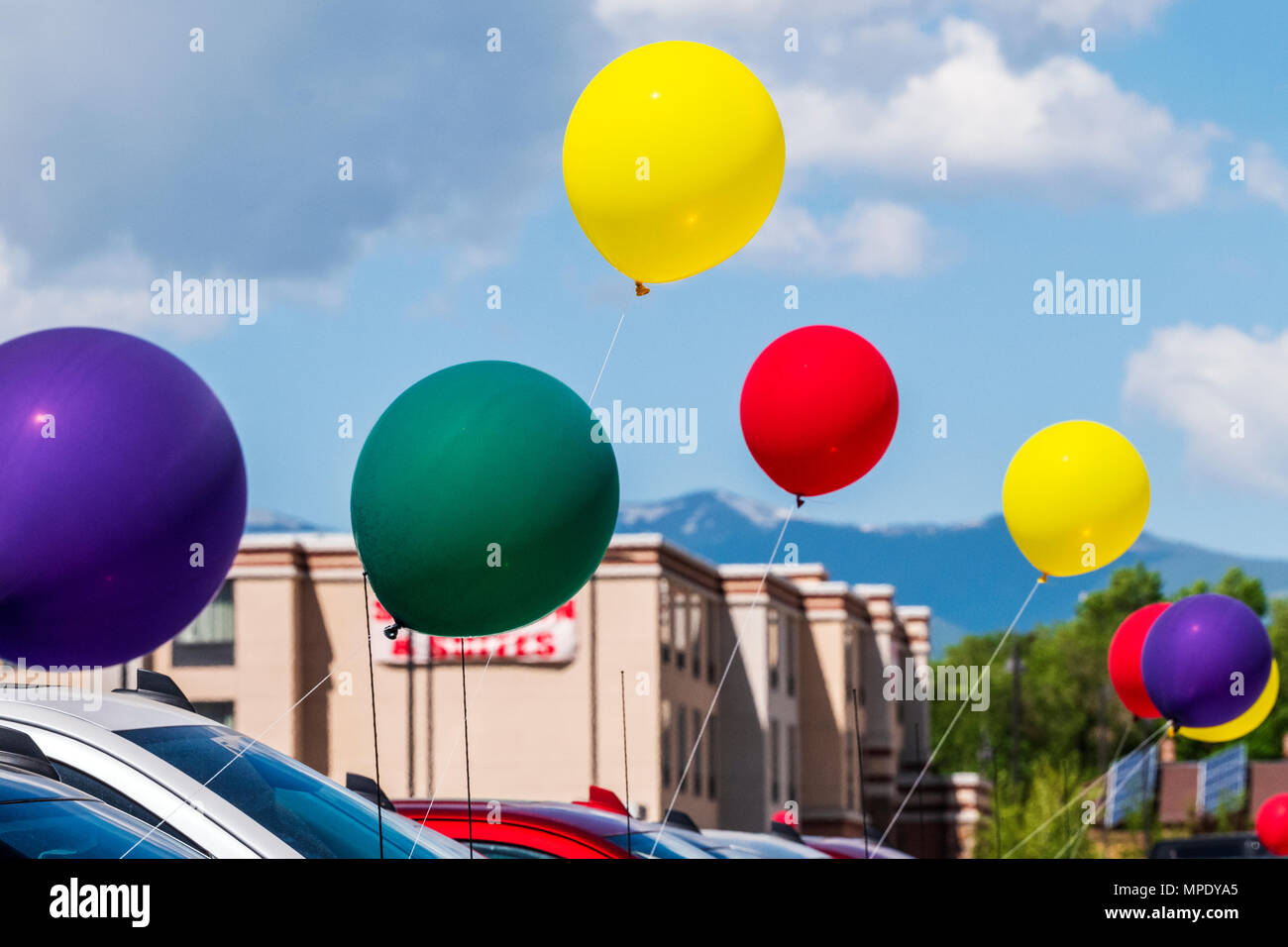 Colorful balloons; windy day; automobile dealership; Salida; Colorado; USA - Stock Image