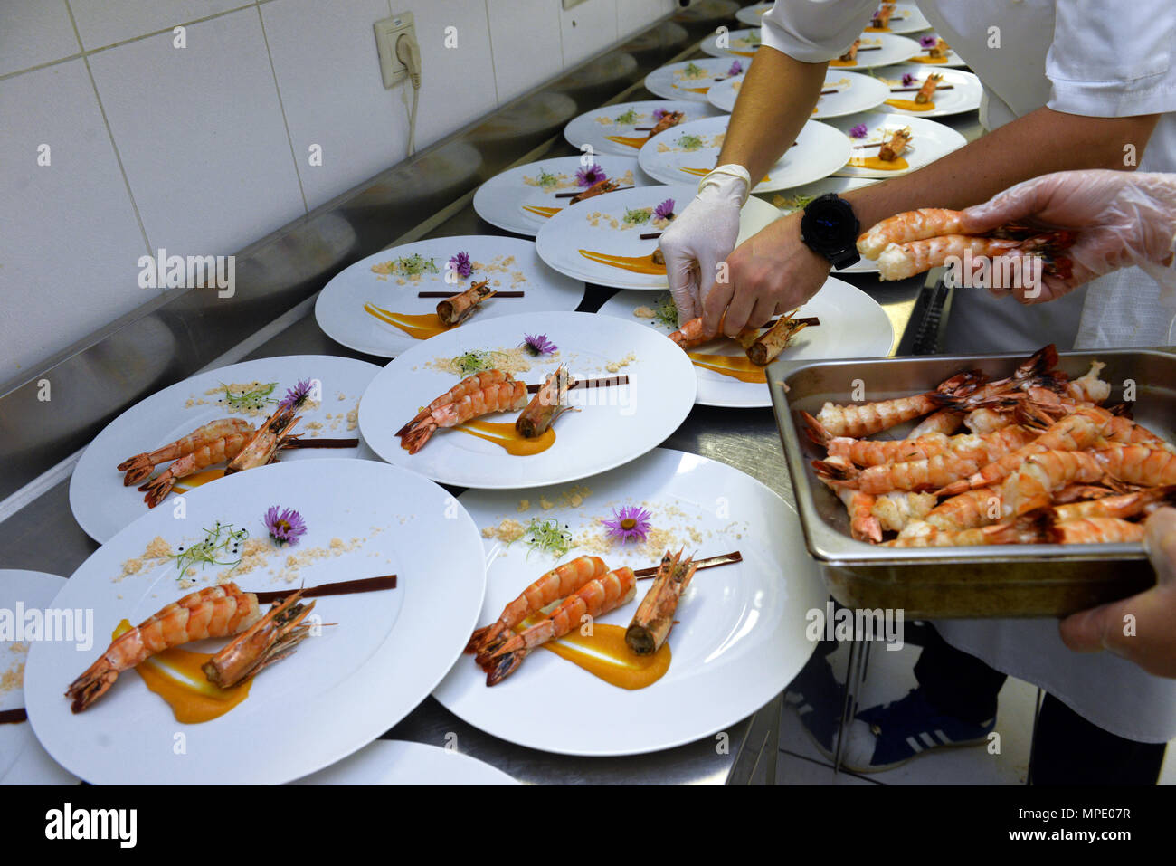 srimps on a white plate on restaurant kitchen - Stock Image