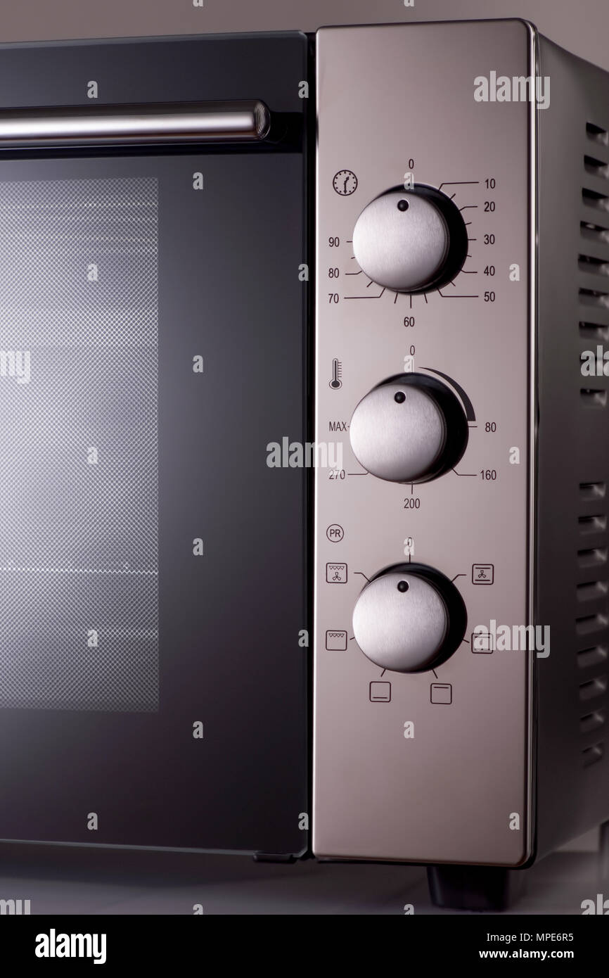 thermostat and handles on a modern microwave. kitchen equipment - Stock Image