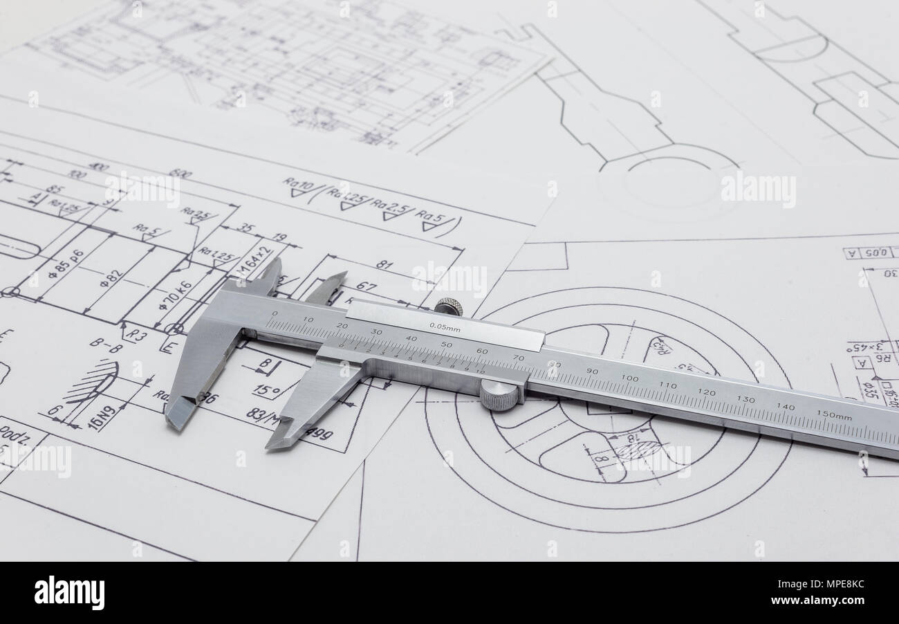 Vernier caliper lying on mechanical scheme. - Stock Image