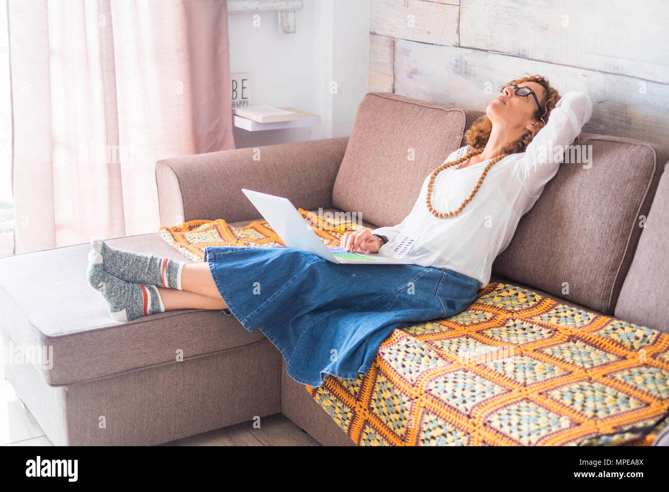 tired or full of thoughts caucasian lonely woman work at home with modern laptop colored keyword like artist way and lifestyle. lay down on the sofa l - Stock Image