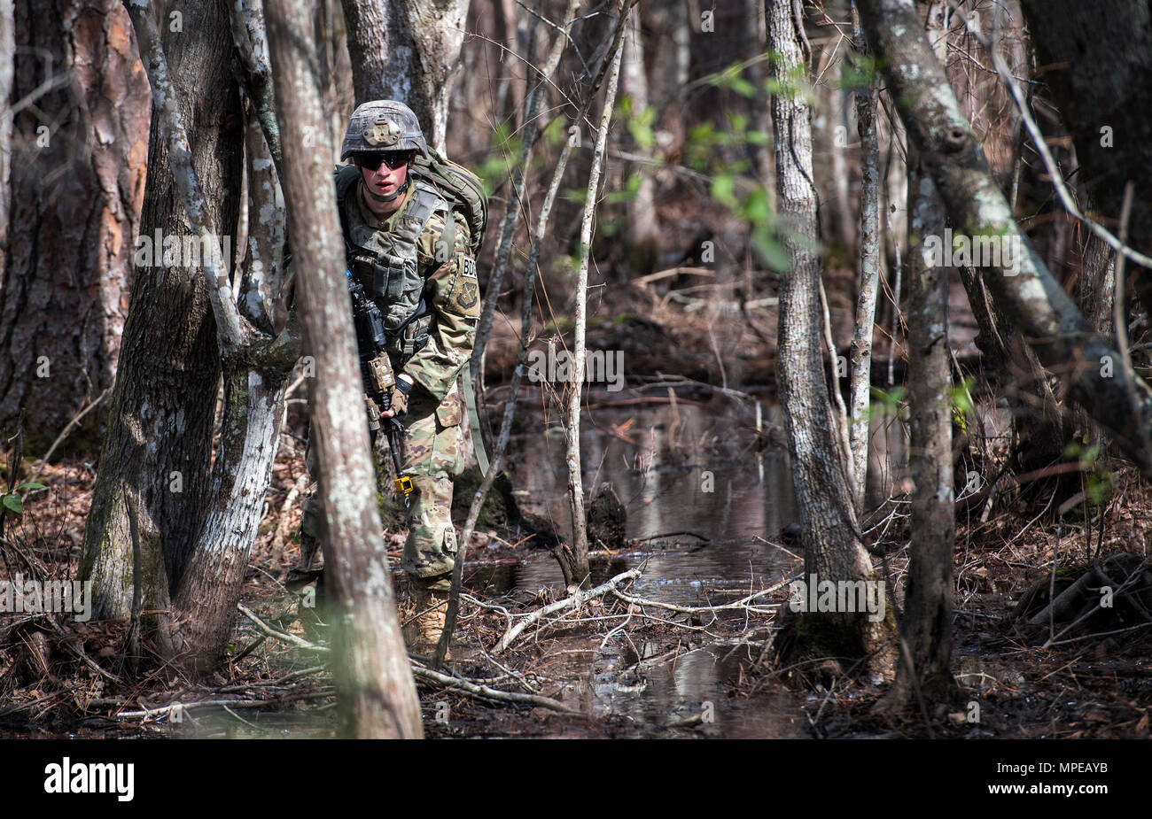 Airman 1st Class Daniel Ross, 822d Base Defense Squadron fireteam member, looks for signs of improvised explosive devices, while simulating patrolling an area outside the wire Feb. 7, 2017, at Moody Air Force Base, Ga. Airmen simulated various missions they would be tasked to complete during a deployment, including being ambushed while out on patrol, gathering intelligence from residents in the local village and raiding buildings. (U.S. Air Force photo by Airman 1st Class Janiqua P. Robinson) - Stock Image