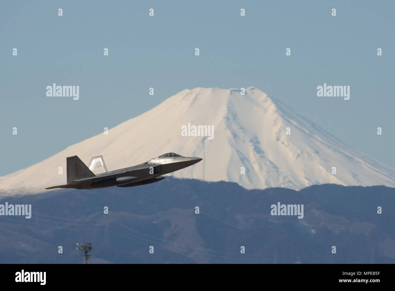 A U.S. Air Force F-22 Raptor from the 90th Fighter Squadron at Joint Base Elmendorf-Richardson, takes off at Yokota Air Base, Japan, Feb. 13, 2017. The F-22 Raptors stopped at Yokota AB before traveling on to Royal Australian Air Force Base, Tindal. As the Air Force's Western Pacific airlift hub, Yokota supports transient aircraft as they conduct mission throughout the Indo-Asia Pacific Region. (U.S. Air Force photo by Yasuo Osakabe/Released) - Stock Image