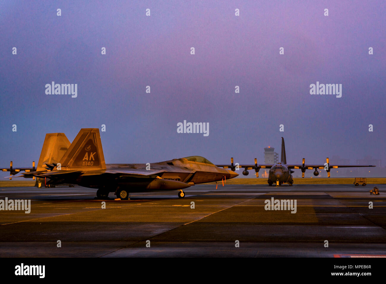 A U.S. Air Force F-22 Raptor from the 90th Fighter Squadron at Joint Base Elmendorf-Richardson, sits on the flight line at Yokota Air Base, Japan, Feb. 10, 2017. The F-22 Raptors stopped at Yokota AB before traveling on to Royal Australian Air Force Base, Tindal. As the Air Force's Western Pacific airlift hub, Yokota supports transient aircraft as they conduct missions throughout the Indo-Asia Pacific Region. (U.S. Air Force photo by Airman 1st Class Donald Hudson) - Stock Image