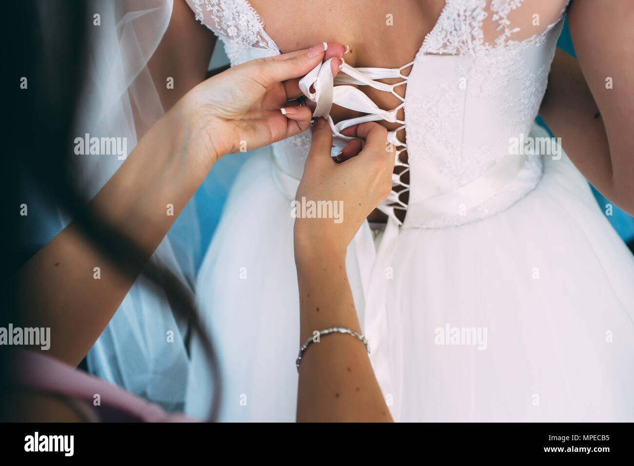 woman helps dress a bride on her wedding day, selective focus - Stock Image