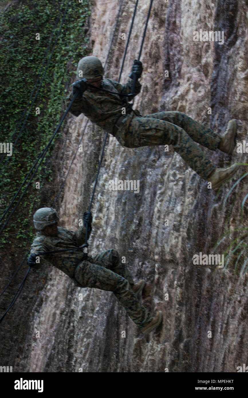 Marines with Golf Co., Battalion Landing Team, 2nd Battalion, 5th Marines, 31st Marine Expeditionary Unit, rappel down a cliff at the Jungle Warfare Training Center, Camp Gonsalves, Okinawa, Japan, Feb. 14, 2017. JWTC exposes Marines to training situations and environments unique to the Indo-Asia-Pacific region which sustain operational readiness and enhance forward deployed capabilities. As the Marine Corps' only continuously forward-deployed unit, the 31st MEU air-ground-logistics team provides a flexible force, ready to perform a wide range of military operations, from limited combat to hum - Stock Image