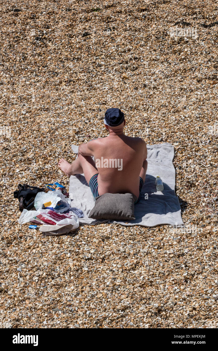 a man sitting on a stony beach with pebbles on a towel on a hot summers day with warm weather sunbathing wearing  baseball cap. older man on beach sun - Stock Image