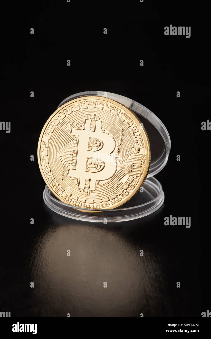 Golden bitcoin in transparent coin container on black, clipping path - Stock Image