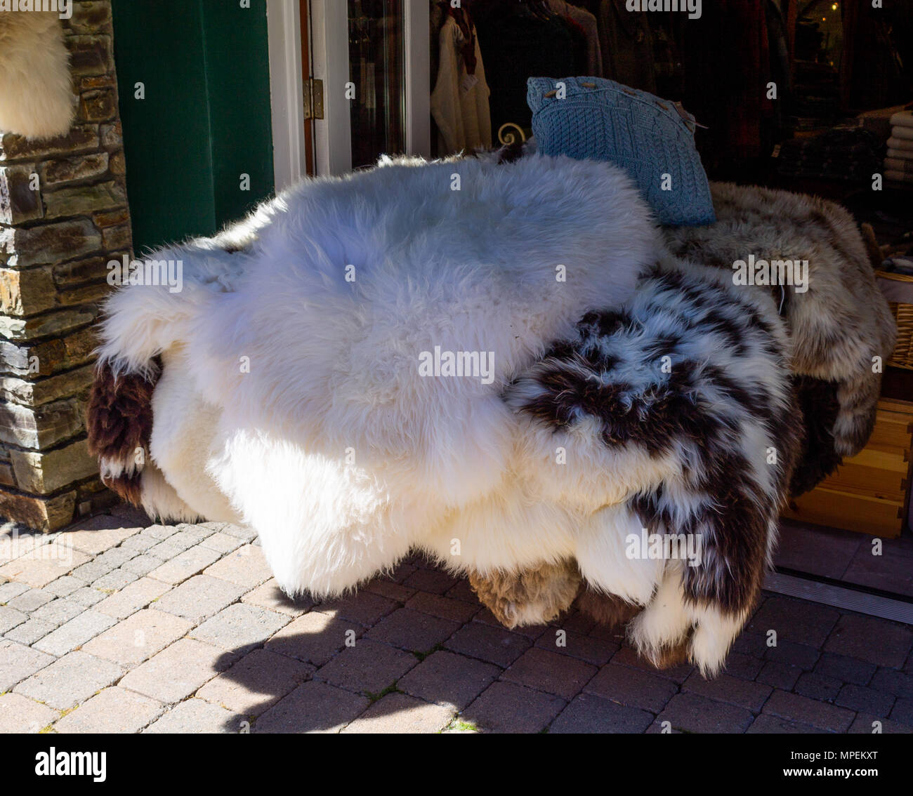 sheepskin rugs of various colours for sale outside a tourist shop in glengariff , Ireland. - Stock Image