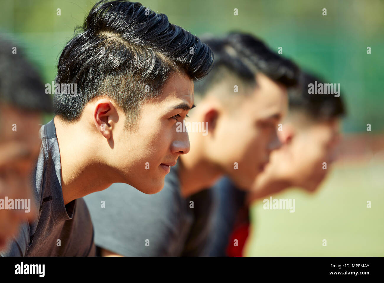 close-up of faces of young asian adult runners on starting line. - Stock Image